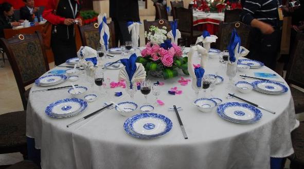 郑州会议场地中餐摆台就是在餐台上摆放各种餐具的过程。中餐餐台通常摆放的餐具、用具有骨碟、勺垫、瓷勺、筷子架、筷子、各种中式酒杯、牙签盅、烟灰缸等。 1.摆台要求与标准 (1)摆台要求摆台操作前,应将双手进行清洗消毒,对所需的餐、饮用具进行完好的检查,不得使用残破的餐、饮用具。 (2)摆台标准餐、酒用具的摆放要相对集中,各种餐、酒用具要配套齐全;摆放时距离相等,图案、花纹要对正,做到整齐划一,符合规范标准;做到既清洁卫生,又有艺术性;既方便宾客使用,又便于服务人员服务。 2、摆台需要的餐、酒具 以10人坐